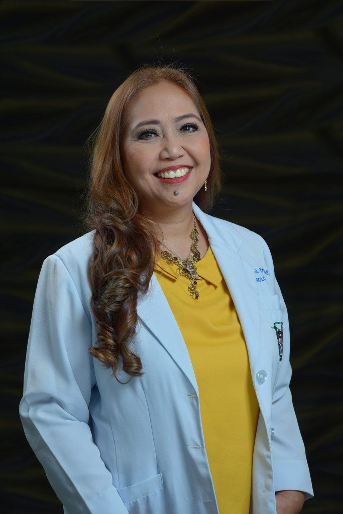 Upper body shot of Belen Dofitas standing in front of a black backdrop. She has long dark brown hair that does down to her waist. She wears a blue jacket over a yellow top.