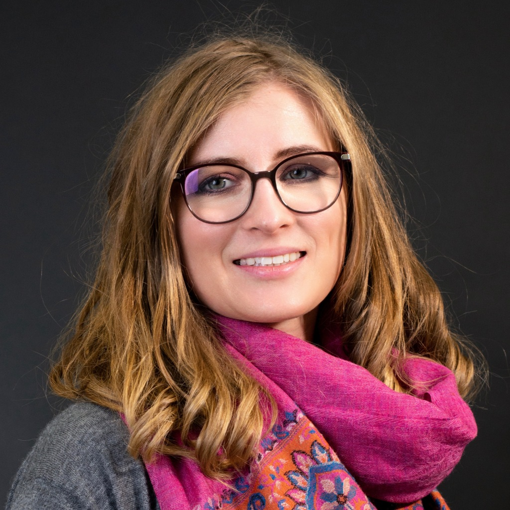 Head shot of Anita Starzyk wearing a pink scarf and standing in front ofa  black background