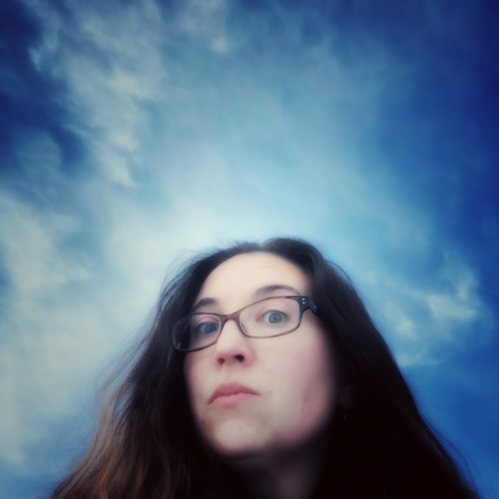 head shot of Danielle Lorzen, the photo is taking from a below angle looking up at Daneille. The background is blue with white clouds
