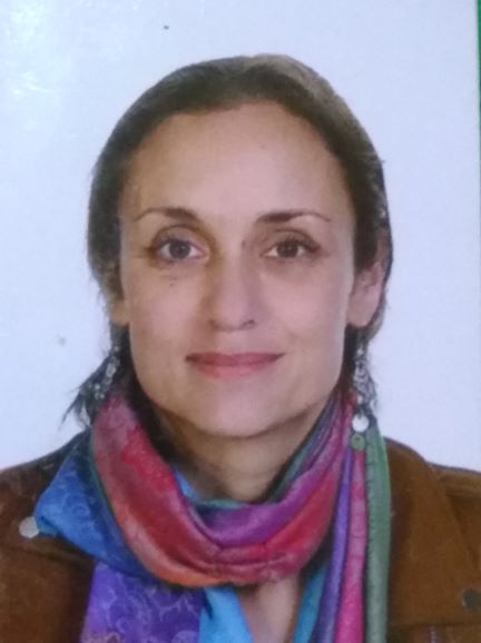 head shot of Julia Daniels wearing a colourful scarf  in front of a white background