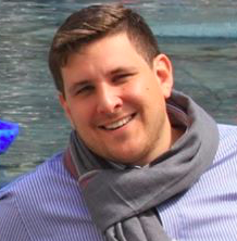 head shot of Mark A. Castrodale wearing a grey scarf standing in front of a blued background