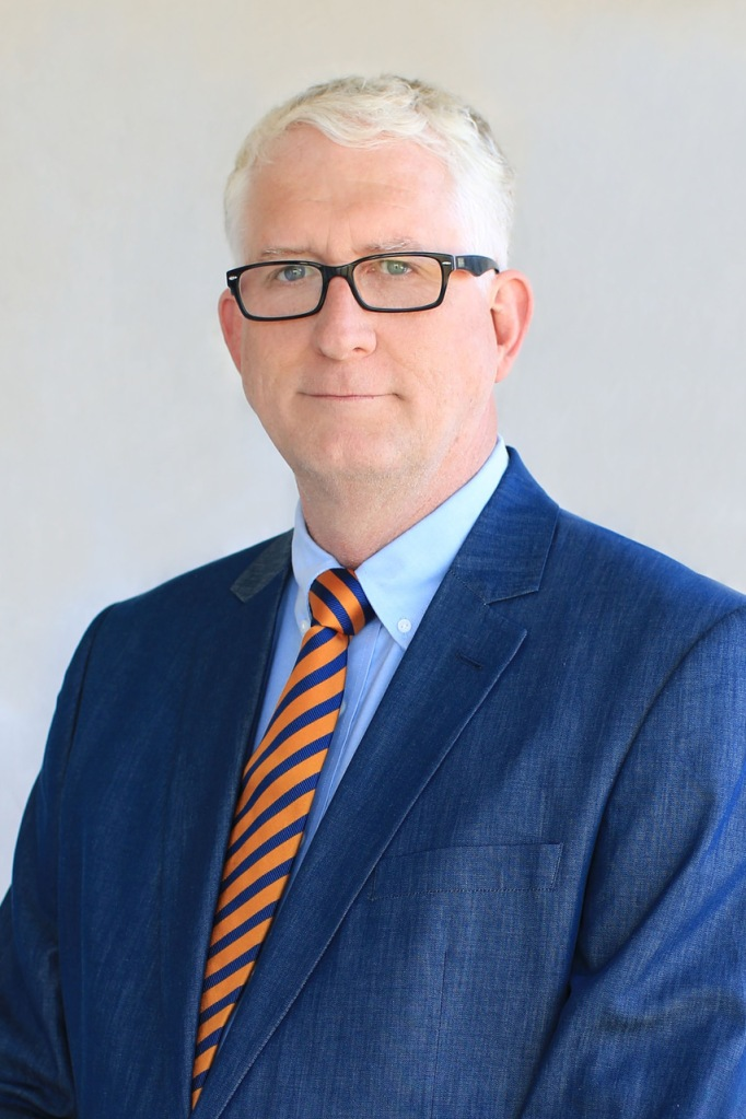 Upper Body shot of Rob Austin, a white man with white hair and glases wearing a blue jacket and an orange-black striped tie.