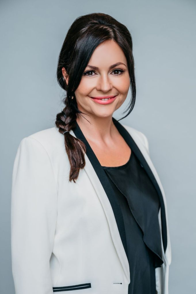 upper body shot of Oana Branzei, a black-haired woman wearing a dark top and a white jacket.